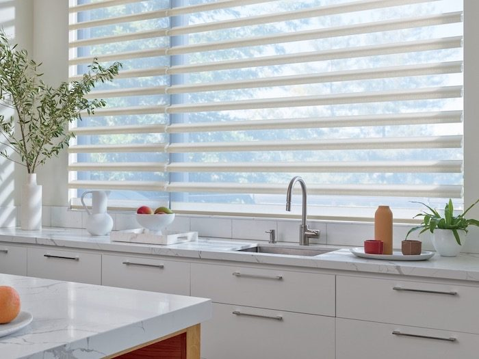 A kitchen with hard surfaces and soft window coverings.